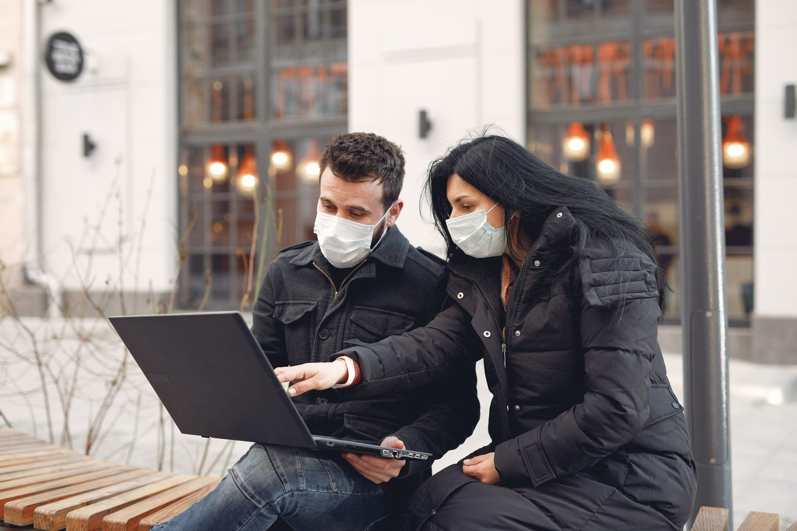 photo of man and woman wearing COVID-19 face masks working on laptop